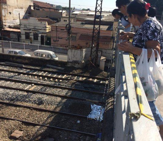 Pessoas observam corpo do jovem sobre a linha do trem próximo à estação Riachuelo, Zona Norte do Rio (Foto: Alba Valéria Mendonça/G1)